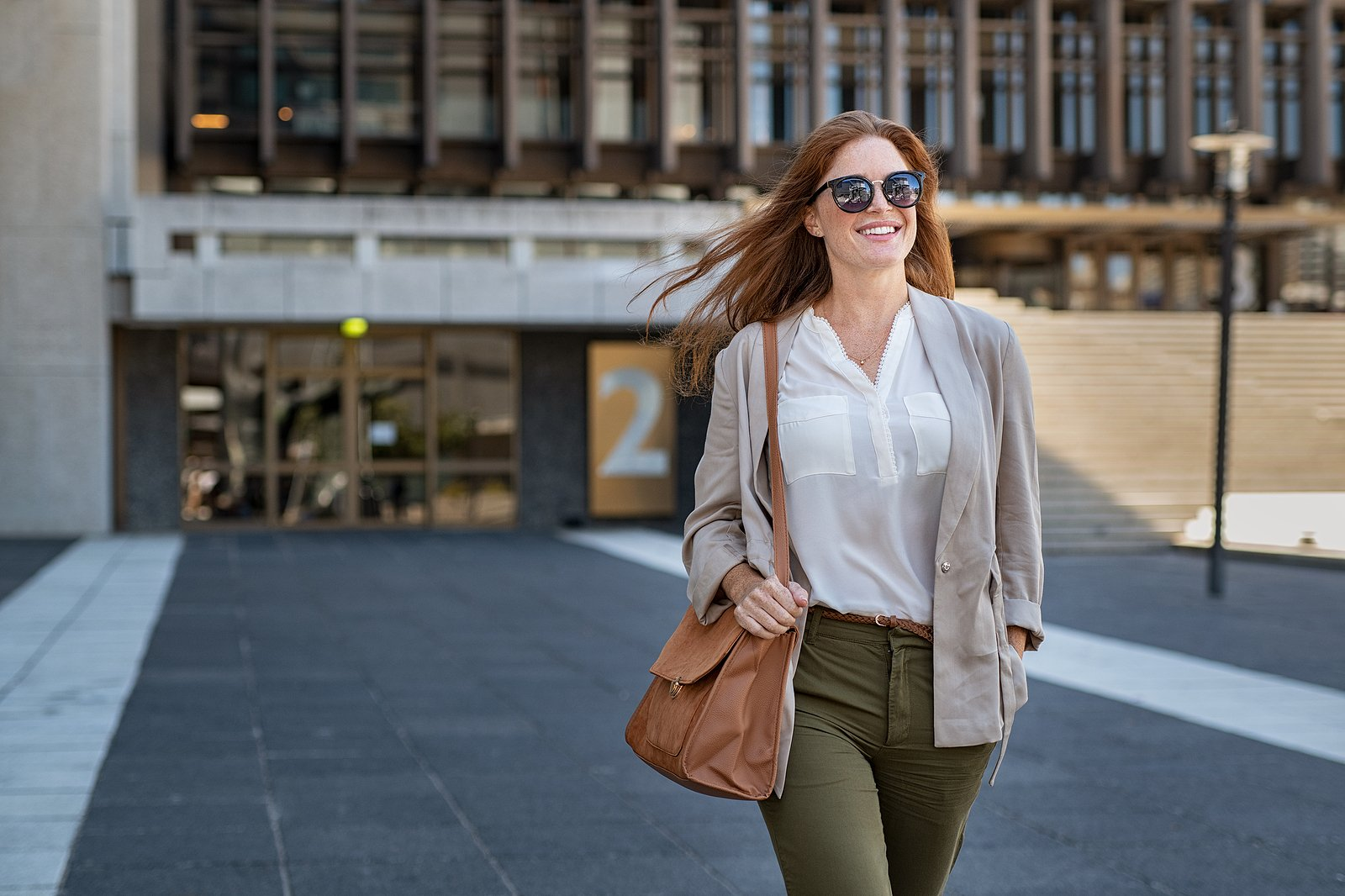 Smiling businesswoman walking away from a large office.