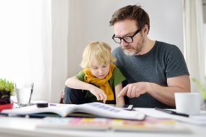 Father Helping Child Do Homeschooling At Home.